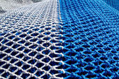Blue and white fishing ntes with rope knots — Stock Photo