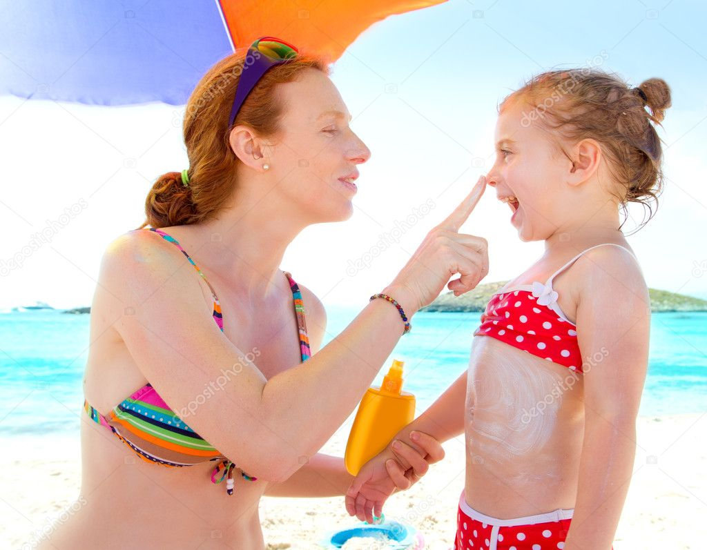 Daughter and mother in beach with sunscreen in bikini  Stock Photo #7315552