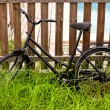 Black grunge bicycle aged on a wood fence — Foto Stock