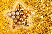 Christmas baubles in star shape on golden — Stock Photo
