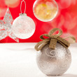 Christmas silver bauble and star on snow red — Stock Photo