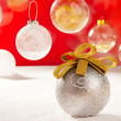 Stock Photo: Christmas silver bauble with golden loop on snow