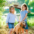 Kid girls with Golden retriever puppy outdoor — Stock Photo