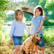 Stock Photo: Kid girls with Golden retriever puppy outdoor