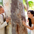 Couple happy in love playing in a tree trunk — Stock Photo