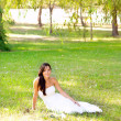 Bride woman sitting in park green grass — Stock Photo