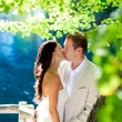 Couple in love kissing in forest tree blue lake — Stock Photo