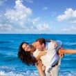 Couple in love piggyback playing in beach — Stock Photo
