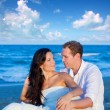 Couple in love sitting in blue beach — Stock Photo