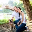 Beautiful couple with puppy in the river — Stock Photo
