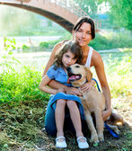 Daughter and mother with golden retriever — Stockfoto