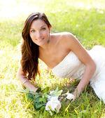 Mulher de noiva deitado na grama do parque — Fotografia Stock