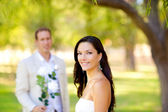 Couple just married with man holding flowers — Stock Photo