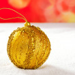 Christmas golden bauble on snow and red — Stock Photo