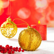 Christmas card of golden baubleand candle — Stock Photo