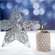 Christmas card of silver star and candle on snow — Stockfoto