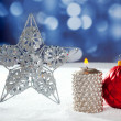 Christmas card of silver star bauble and candle - Stock Photo