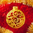 Christmas card golden bauble and tinsel - Stock Photo