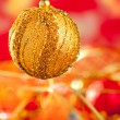 Christmas card of golden bauble and red blur — Stock fotografie