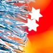 Christmas tinsel stars silver blue on red — Stock Photo