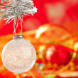 Christmas tinsel snow crystal bauble on red — Stock Photo