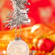 Christmas tinsel snow crystal bauble on red - Stock Photo