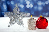 Christmas card of silver star bauble and candle — Stock Photo