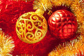 Christmas card golden bauble and tinsel on red — Stock Photo