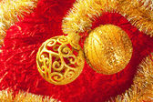 Christmas card golden bauble and tinsel on red — Photo