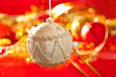 Christmas card of white velvet bauble on red — Stock Photo