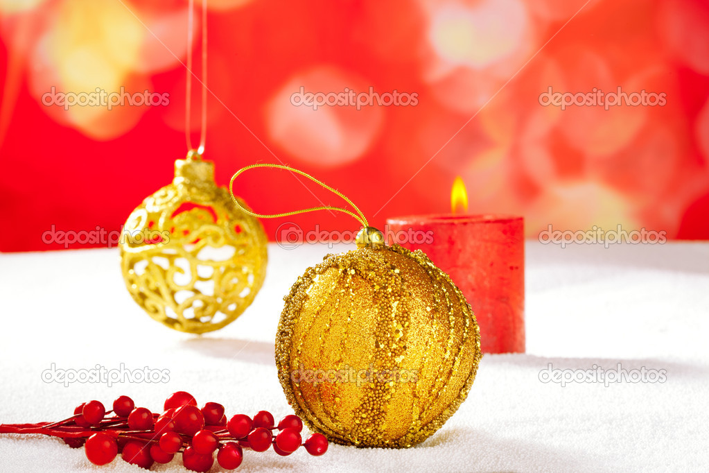 Christmas card of golden baubleand candle on snow — Stock Photo #7495405