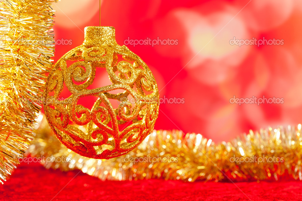 Christmas card golden bauble arabesque and tinsel on red background — Stock Photo #7496228