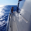 Boat side sailing in blue sea sun reflection - Stock Photo