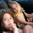Stock Photo: Little girls inside car eating candy stick