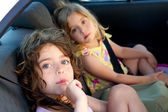 Little girls inside car eating candy stick — Stock Photo