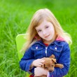 Blond kid girl with puppy pet dog in green grass — Stock Photo #7650966