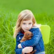 Blond kid girl with puppy pet dog in green grass — Stock Photo #7651021