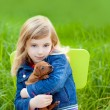 Blond kid girl with puppy pet dog in green grass - Stock Photo