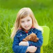 Blond kid girl with puppy pet dog in green grass — Stock Photo #7651132