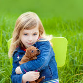 Blond kid girl with puppy pet dog in green grass — Stock Photo
