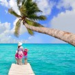 Daughters and mother in jetty on tropical beach — Stock Photo