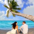 Couple in love sitting in blue beach - Stok fotoğraf