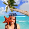 Latin tourist girl holding starfish tropical beach — Stock Photo