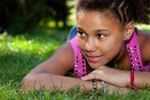 Young black teenage girl lying on the grass — Stock Photo
