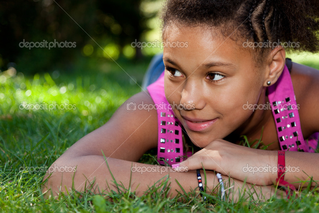 Stock Photo of Young black teenage girl lying on the grass