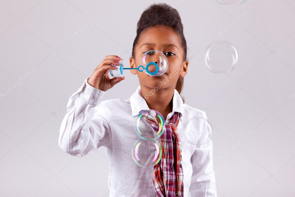 Cute little African American girl blowing soap bubbles — Stock Photo #7228619
