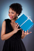 Young African American woman holding a gift — Stock Photo