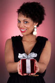 Young African American woman offering a gift — Stock Photo