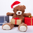 Seated teddy bear wearing a santa hat — Stock Photo