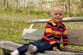 Un ragazzo seduto su una panchina — Foto Stock